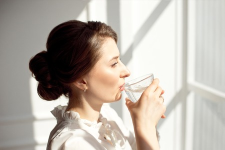 Young beautiful girl in a white shirt is standing near a window in a working office and drinking pure mineral water from a glass cup.
