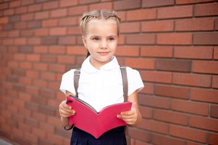 Niña con cabello rubio con camisa blanca y falda azul sostiene un tablero vacío cerca de la pared superior.