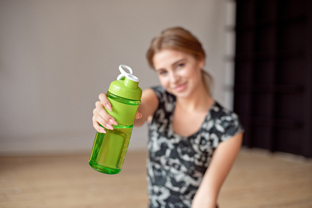 cropped image of sporty woman holding bottle of water. 版權商用圖片