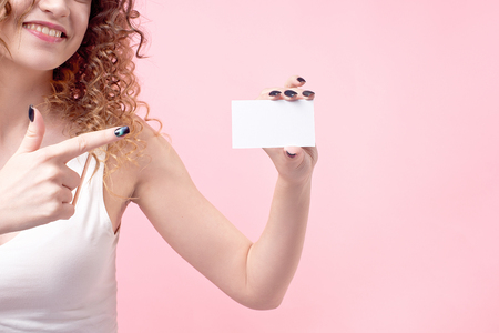 young beautiful girl with curly hair holds a card in her hand and shows it. 版權商用圖片