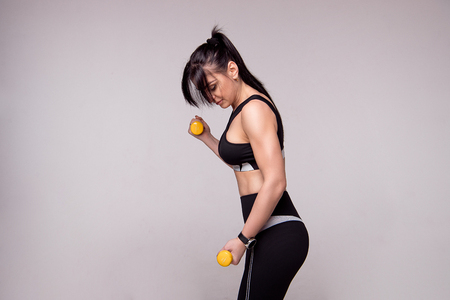 Portrait of a sporty young European fitness woman doing workouts with dumbbells isolated on gray background. Stock Photo