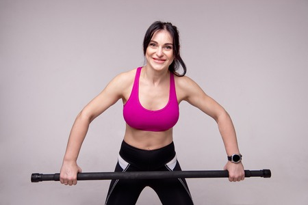 Beautiful muscular woman doing exercise with gymnastic stick on a gray background.