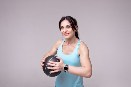 Beautiful sporty woman doing squats with med ball isolated on white background. Fitness and healthy lifestyle