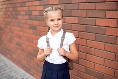 Niña con cabello rubio con camisa blanca y falda azul sostiene un tablero vacío cerca de la pared superior