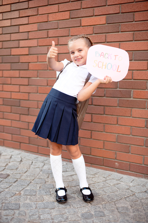 A little girl blonde in school uniform stands near a brick wall holding a blackboard with the text back to school