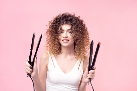Beautiful woman with amazing curls in white shirt holds styling accessories in hand. Hair styling set with curling accessories.