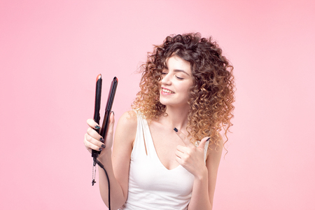 Beautiful woman with a smile on her face with amazing curls in a white t-shirt holds in her hand accessories for styling and curling hair. Imagens