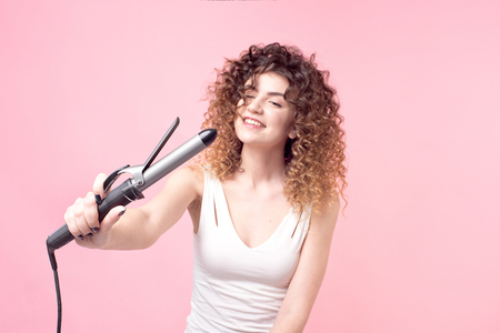 Charming girl with a smile on her face curly hair in a white T-shirt with curling irons.