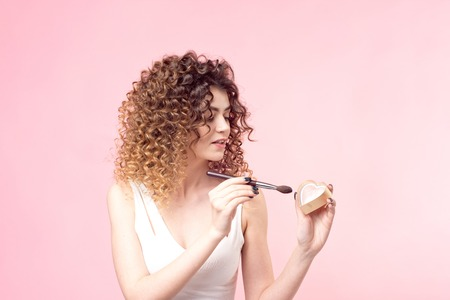 Beautiful young woman applying foundation powder or blush with makeup brush.