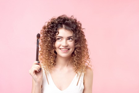 Cheerful happy woman sitting with a makeup brush while working in the beauty salon.