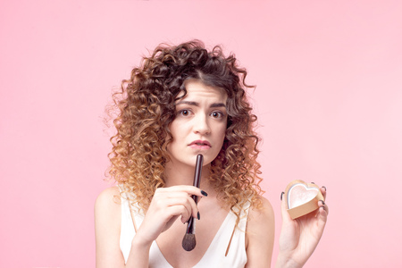 Cheerful happy woman sitting with a makeup brush while working in the beauty salon. Imagens
