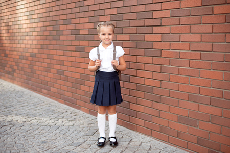 Full-length of a little smiling girl in school uniform posing against a school entrance background