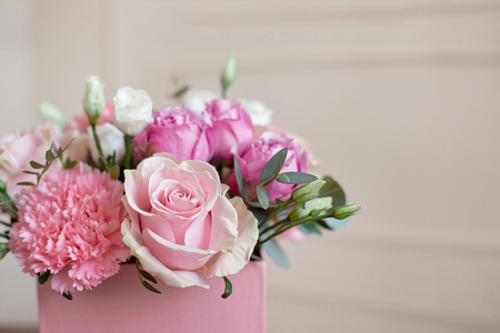 Elegante bouquet da sposa sposa di rose rosa, garofano bianco e fiori verdi e verdi con nastri sdraiati sul tavolo pastello. Archivio Fotografico