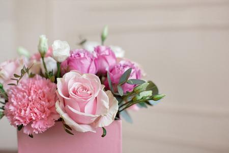 Novia elegante ramo de la boda de rosas rosadas, clavel blanco y flores verdes y verdes con cintas en la mesa de pastel. Foto de archivo
