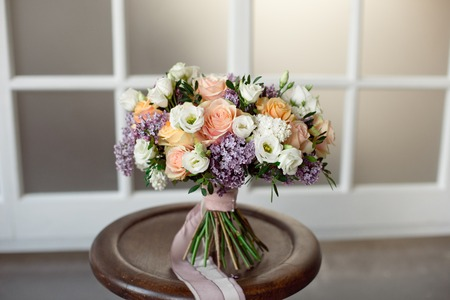 Vintage rustic bouquet of wild roses Carnations with green leaves of eucalyptus and thistle of lilac twigs on a light background.