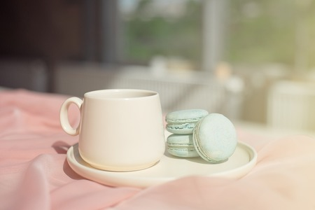 French macaroon blue plate on the pink and coffee cup standing on a wooden table with pink tablecloth white vase with flowers roses and greens. Imagens