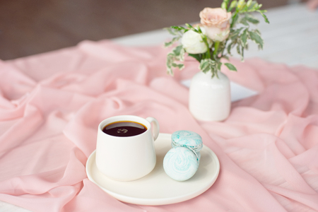 French macaroon blue plate on the pink and coffee cup standing on a wooden table with a pink tablecloth white vase with flowers roses and greens