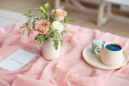 French macaroon blue plate on the pink and coffee cup standing on a wooden table with a pink tablecloth white vase with flowers roses and greens Imagens - 124847657