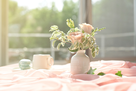 French blue macaroon plate and coffee cup standing on a wooden table with a pink tablecloth white vase with flowers roses and greens
