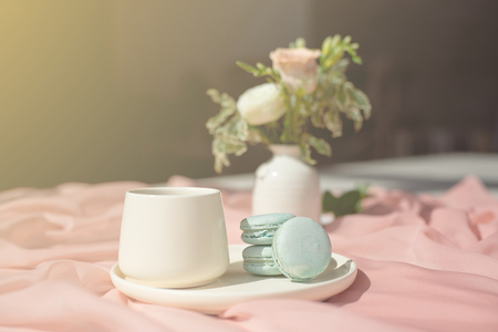 French macaroon blue plate on the pink and coffee cup standing on a wooden table with pink tablecloth white vase with flowers roses and greens. Imagens - 124847666