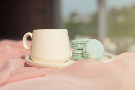 French blue macaroon and coffee cup standing on a wooden table with a pink tablecloth white vase with flowers roses and greens