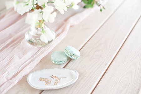 Sweet french macaroons on wood flat lay copyspace. Top voew on set of three purple macaroons on wooden board, lying diagonally on wooden table, void.