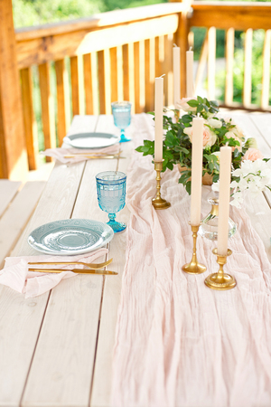 Decorated table for dinner for two person, with plates knife, fork, cheese, wine, wine glasses and flowers in a copper vase