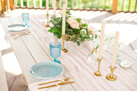 Decorated table for dinner for two person, with plates knife, fork, cheese, wine, wine glasses and flowers in a copper vase 版權商用圖片 - 124710274