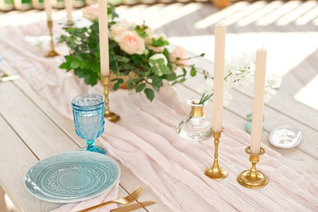 Decorated table for dinner for two person, with plates knife, fork, cheese, wine, wine glasses and flowers in a copper vase 版權商用圖片 - 124710279