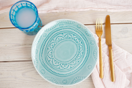 Table for guests, decorated with candles, served with cutlery and crockery and covered with a tablecloth blue plate and golden fork and knife on pink gauze napkin. 版權商用圖片 - 124710278