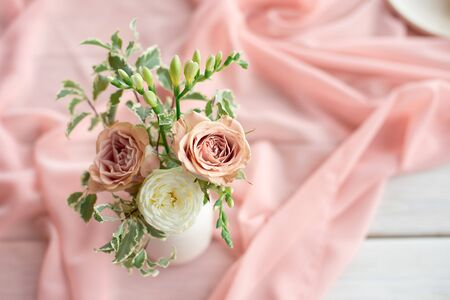 Magnificent bouquet of different flowers is a floral arrangement in a white ceramic vase of a round shape. Table setting is lilac and peach