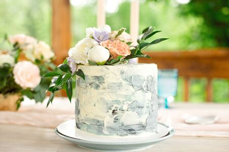 Wedding decoration table in the garden, floral arrangement, In the style vintage on outdoor. Wedding cake with flowers. Decorated table with flowers, served for two people
