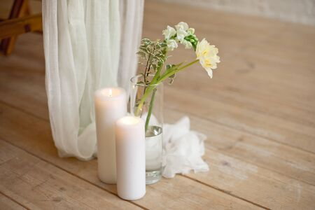 Branch of blooming white peony tulip Mattiola branch in a glass vase white wax candles stand on the wooden light floor indoors.