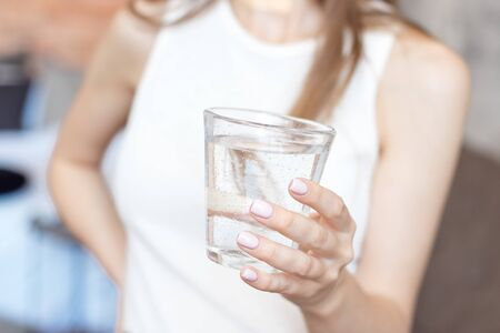close-up woman with slim body holding a glass of water, rear veaw. Imagens - 126030456