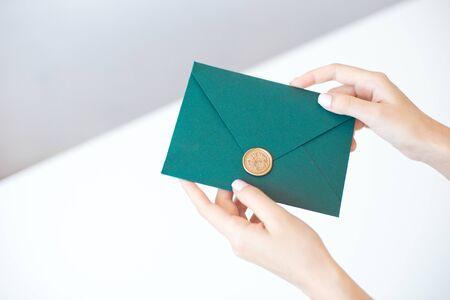Photo en gros plan de mains féminines tenant une enveloppe d'invitation verte avec un sceau de cire, un certificat-cadeau, une carte postale, une carte d'invitation de mariage.