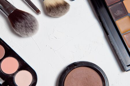 Professional makeup brushes for the highlighter of the foundation for make-up of the rouge blush coloring on a gray textured background.