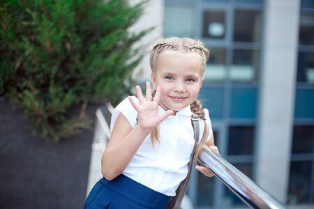 La ragazza sorridente felice sta andando a scuola per la prima volta con la borsa va alla scuola elementare Archivio Fotografico