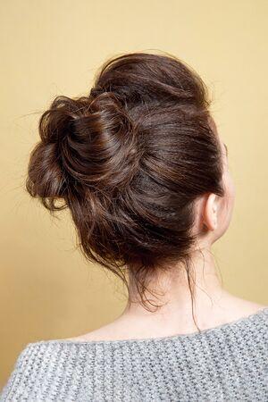 Vue arrière du chignon moyen de coiffure féminine sur de longs cheveux bruns raides avec un volume radical.
