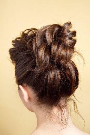 Vue arrière du chignon moyen de coiffure féminine sur de longs cheveux bruns raides avec un volume radical Banque d'images