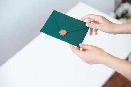 Photo en gros plan de mains féminines tenant une enveloppe d'invitation verte avec un sceau de cire, un certificat-cadeau, une carte postale, une carte d'invitation de mariage. Banque d'images