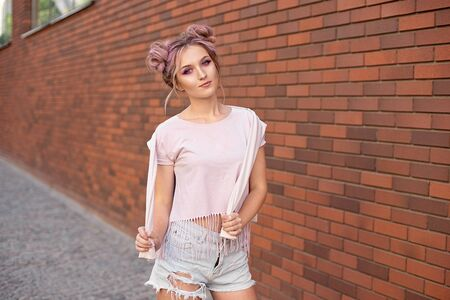 Portrait of a young beautiful girl with pink hair bun smiling against a red brick wall