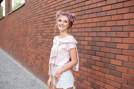 Beautiful smiling woman with clear skin, bright pink make-up and white teeth with hair bun on a red brick background