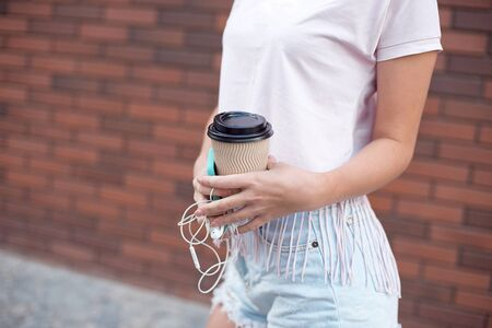 Young woman with mobile phone and coffee on a red brick background