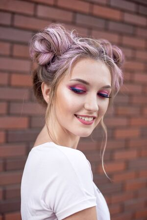 Portrait of a young beautiful girl with pink hair bun. Bright pink make-up smiling against a red brick wall Imagens
