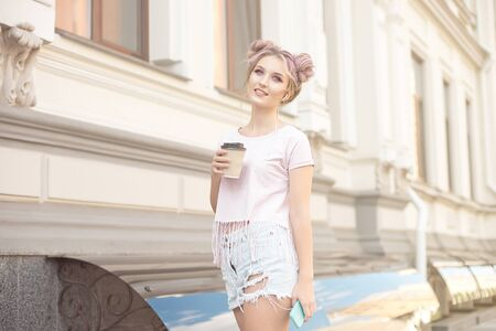 Smiling beautiful girl with pink hair hairstyle walks down the street with a cup of coffee enjoying a beautiful sunny day. Imagens