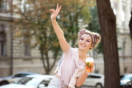 Happy young smile girl in a pink T-shirt and a sweatshirt with a bright make-up and hair bun sitting outside with a summer cocktail Imagens
