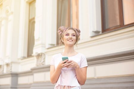 Portrait of a young stylish hipster woman walking down the street dressed in a trendy outfit, a pink hairstyle bun traveling around holding a mobile phone Imagens