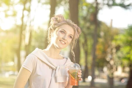 Young beautiful girl drinking fresh juice from plastic takeaway food cups after a walk outdoors. Healthy lifestyle. Smiling slim blonde with pink hair