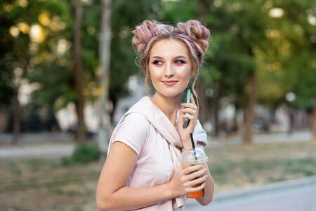 Happy cheerful young blonde with pink hair, walks against the backdrop of the city, calls on a mobile phone to his friends. Blonde student is resting on the street after college to meet friends