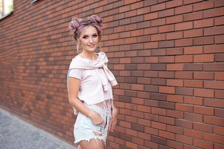 Portrait of a young beautiful girl with pink hair bun smiling against a red brick wall.